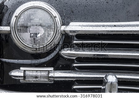closeup of classic car grill and headlamp with wet paint and chrome - stock photo