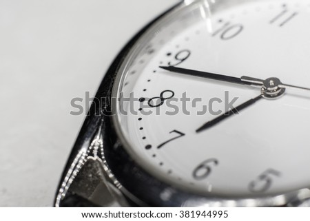 Closeup of clock face with hands, selective focus at the number