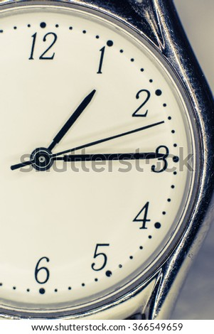 Closeup of clock face with hands, vintage filter - stock photo