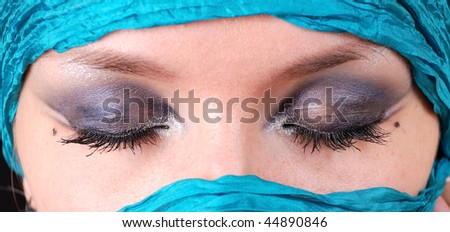 Closeup of closed woman's eyes with east make-up - stock photo