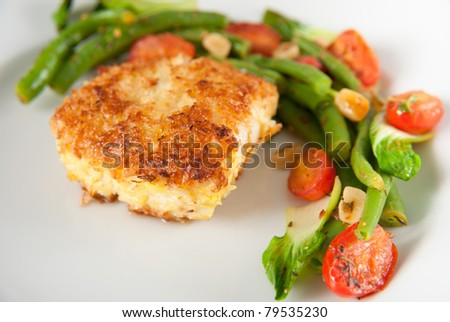 Closeup of Cod Fried  in Coconut Flakes Served with Sauteed Bok Choy, Green Beans and Tomatoes - stock photo