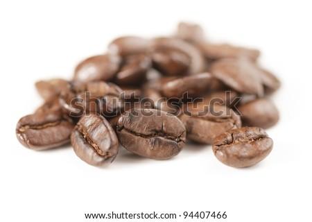 Closeup of coffee bean heap with critical focus on front center bean. - stock photo