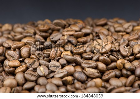 Closeup of coffee beans on black background - stock photo