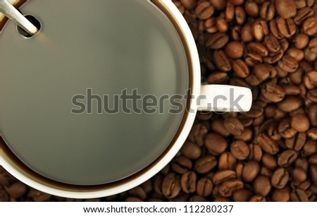 closeup of coffee cup and beans on background