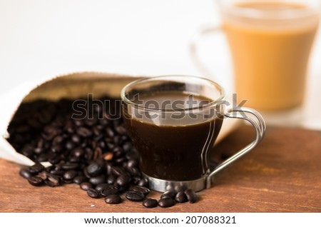 closeup of cofffe cup and coffee beans in a bag with a latte on the background selective focus - stock photo
