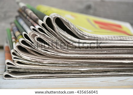 Closeup of color stacked  journal newspapers on a wooden table background