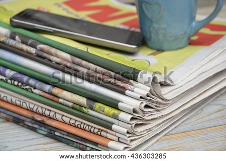 Closeup of color stacked newspapers on a wooden table background with mobile phone and coffee cup
