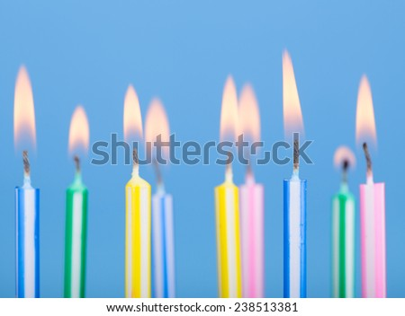 Closeup of colorful birthday candles on a blue background
