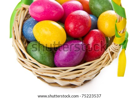 closeup of colorful easter eggs in basket isolated