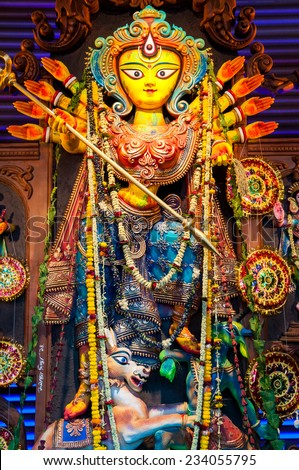 Closeup of colorful idol of Goddess Durga being worshipped with flowers - stock photo