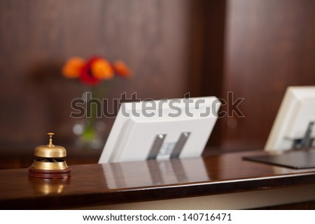 Closeup of computers and bell at reception counter in hotel - stock photo