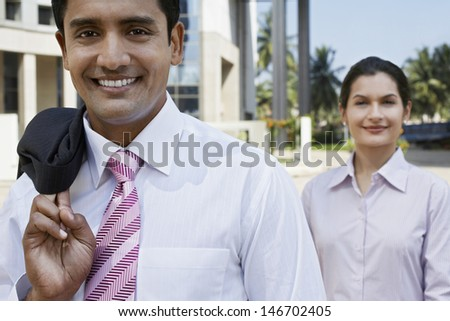 Closeup of confident businessman and businesswoman standing outside building - stock photo