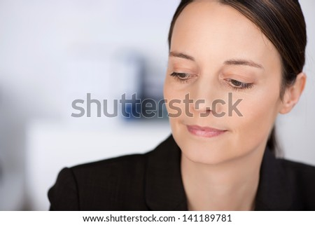 Closeup of confident businesswoman looking down in office - stock photo