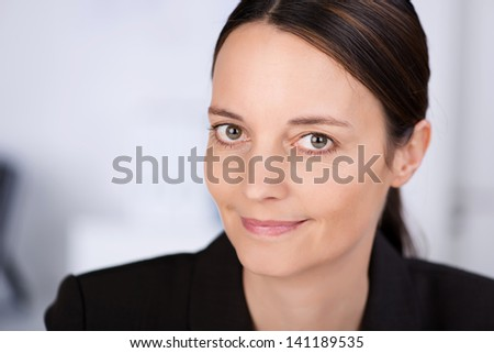 Closeup of confident businesswoman smiling in office - stock photo