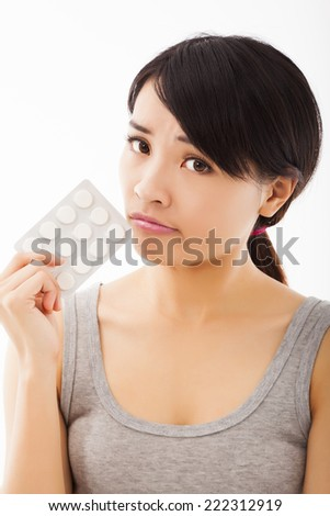 closeup of confused young woman holding pills.isolated on white background - stock photo