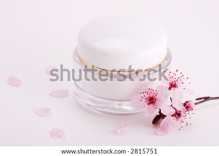 Closeup of container of moisturizing face cream and blooming twig of plum on white background with small pink petals around