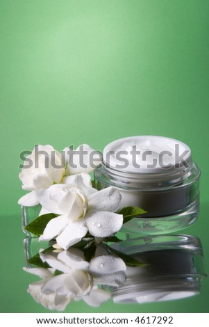 Closeup of container of opened moisturizing face cream and blooming fragrant white gardenias on melted icecubes over green toned background - stock photo