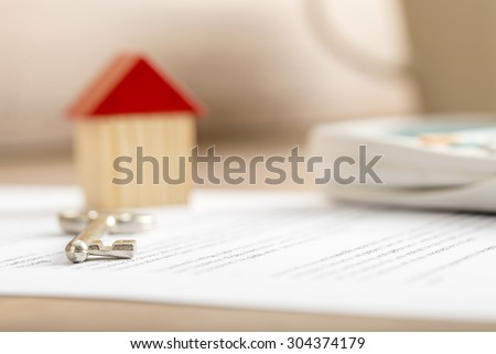 Closeup of contract of house sale ready to be signed with wooden toy house, house key and calculator on it. Conceptual of real estate, mortgage and lease. - stock photo