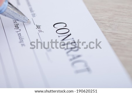 Closeup of contract paper and pen on desk in office