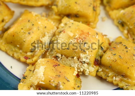 Closeup of cooked ravioli with spices on a plate - stock photo