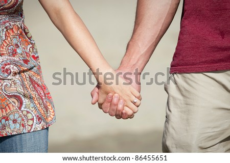 Closeup of couple holding hands - stock photo