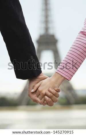 Closeup of couple holding hands in front of blurred Eiffel Tower - stock photo