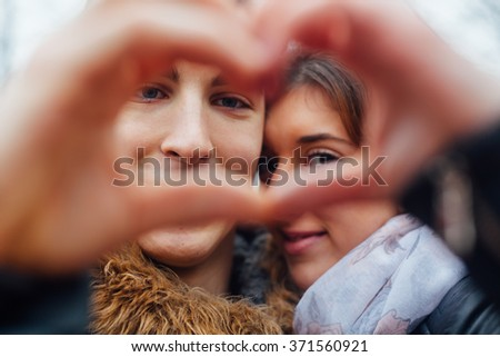 Closeup of couple making heart shape with hands - stock photo