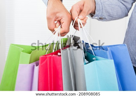 Closeup of couple's hands holding multicolored shopping bags in house - stock photo