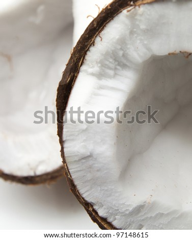 Closeup of cracked coconut on white background with light shadow. Shallow focus depth on front coconut - stock photo