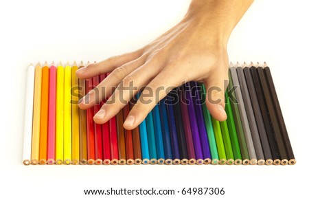 closeup of crayons stack and hand on white background - stock photo