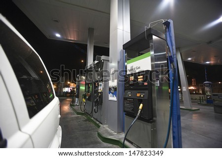 Closeup of cropped car at gas station with view of fuel pumps and natural gas at night - stock photo