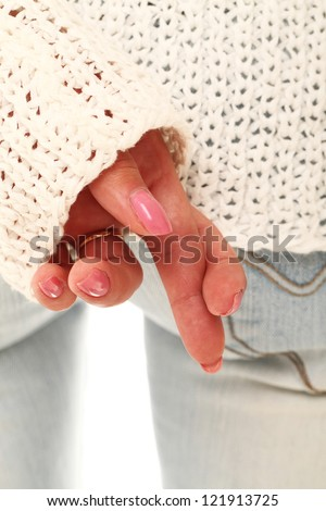 Closeup of crossed fingers behind of women back wearing in sweater and jeans