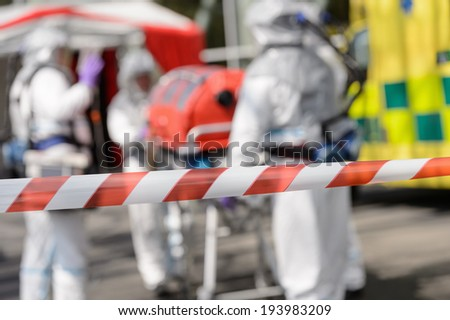 Closeup of crossing barrier tape biohazard medical team in background - stock photo