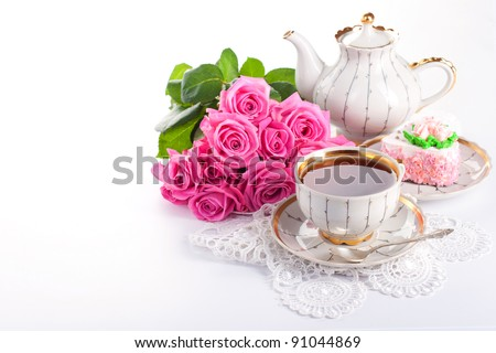 Closeup of cup of tea with cake and roses - stock photo