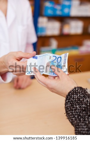 Closeup of customer's hand paying money to pharmacist at counter - stock photo