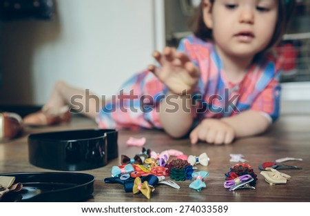 Closeup of cute baby girl playing with hair clips collection lying in a wooden floor at home. Selective focus on hair clips. - stock photo