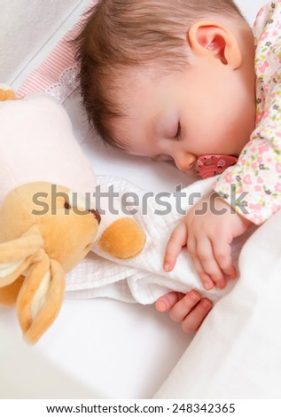 Closeup of cute baby girl sleeping in a cot with pacifier and stuffed toy - stock photo