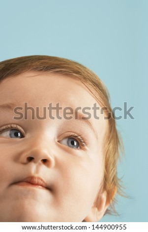 Closeup of cute boy looking away isolated on blue background - stock photo