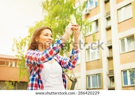 Closeup of cute happy young brunette mixed race woman taking a selfie with smartphone. Teenage girl in blue and red checkered shirt taking a self portrait with cellphone outdoors in urban environment. - stock photo