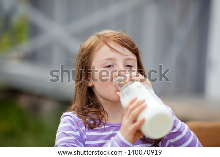 Closeup of cute little girl drinking milk from bottle at campsite - stock photo
