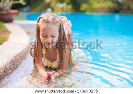 Closeup of Cute little girl in the swimming pool looks at camera - stock photo