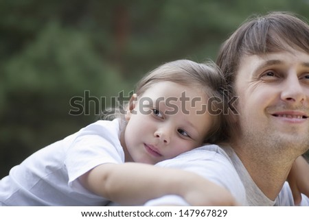 Closeup of cute little girl resting on father's back in park