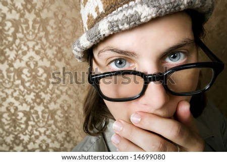 Closeup of Cute Nerdy Woman in a Knit Cap Covering Her Face With Her Hand - stock photo