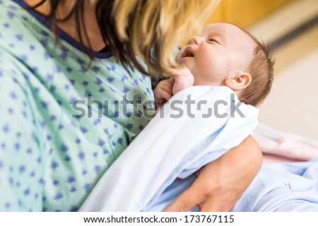 Closeup of cute newborn babygirl being carried by mother in hospital - stock photo