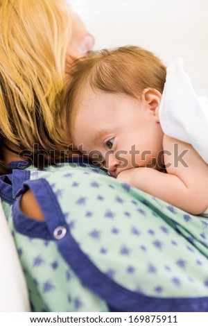 Closeup of cute newborn babygirl lying on mother in hospital - stock photo
