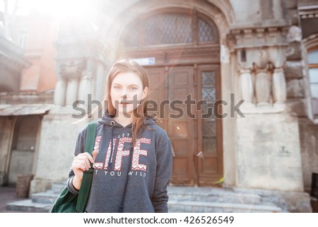 Closeup of cute young woman standing near the doors of house in old city - stock photo