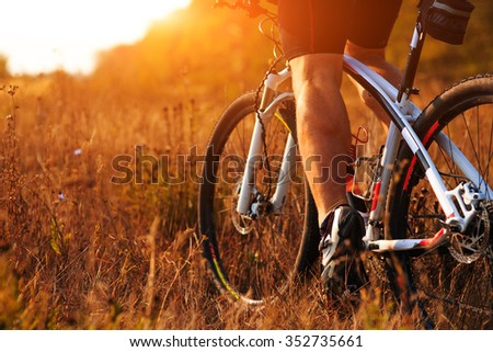 Closeup of cyclist man legs riding mountain bike on outdoor trail in autumn forest - stock photo