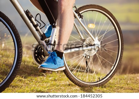 Closeup of cyclist man legs riding mountain bike on outdoor trail in nature - stock photo