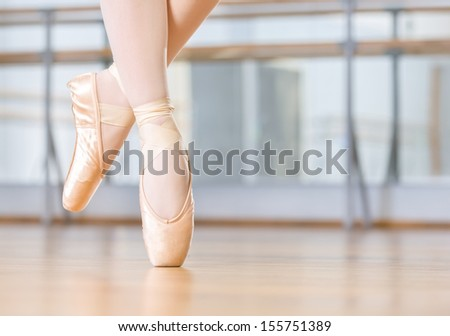 Closeup of dancing legs of ballerina wearing white pointes in the dancing hall - stock photo