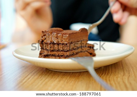 Closeup of dark chocolate mousse on white plate with fork                           - stock photo